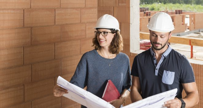 Male and female building professionals with technical drawing in new built construction
