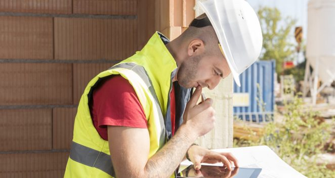 Construction worker working with tablet placed on blueprint in building shell