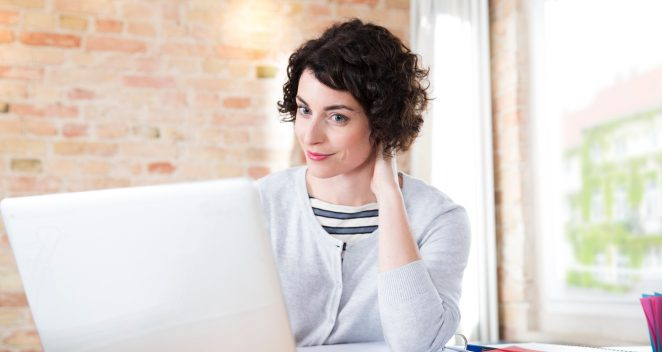 Woman looking at computer screen in front of brick-lined wall